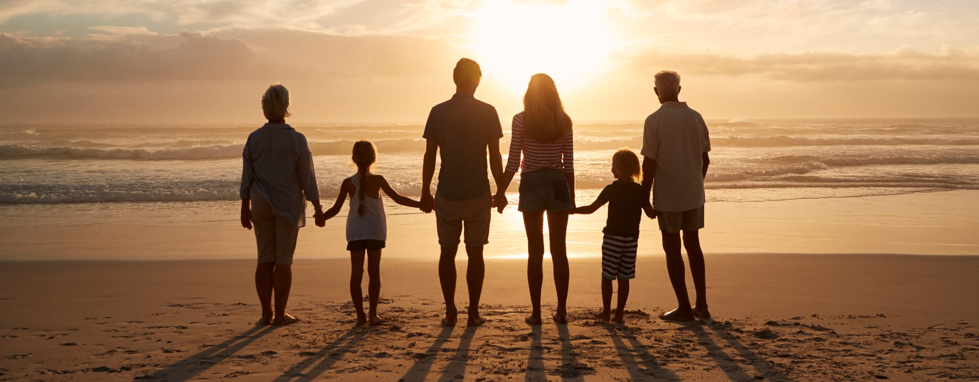 Family on the beach looking at the sunset